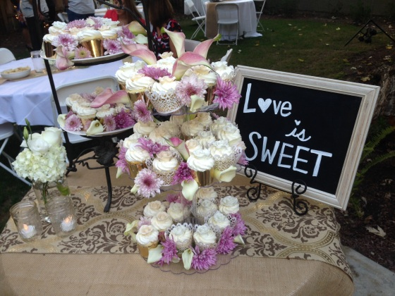 Delicious cupcakes adorned with fresh flowers and a cute Love is Sweet chalkboard on Burlap linens